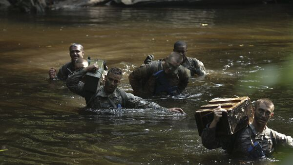 U.S. Army Soldiers assigned to Bravo Co. 3rd Battalion, 7th Infantry Regiment, 2nd Infantry Brigade Combat Team, 3rd Infantry Division carry equipment through a pond during the team obstacle course at the French Jungle Warfare School near Yemen, Gabon, June 9, 2016. - Sputnik International