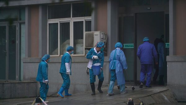 Hospital staff wash the emergency entrance of Wuhan Medical Treatment Center, where some infected with a new virus are being treated, in Wuhan, China, Wednesday, Jan. 22, 2020. - Sputnik International