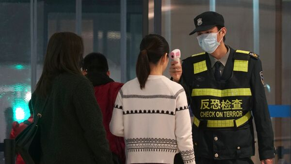 An airport staff member uses a temperature gun to check people leaving Wuhan Tianhe International Airport in Wuhan, China - Sputnik International