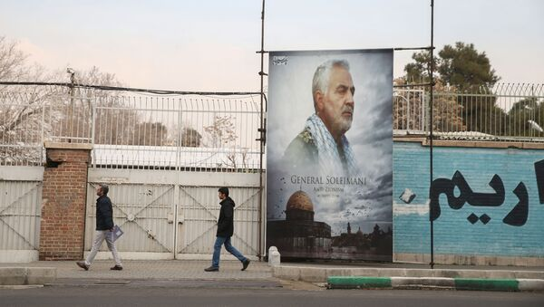 People walk past a picture of Iranian Major-General Qassem Soleimani, head of the elite Quds Force, who was killed in an air strike at Baghdad airport, as it is seen in front of the former U.S. Embassy's building in Tehran, Iran, January 21, 2020 - Sputnik International
