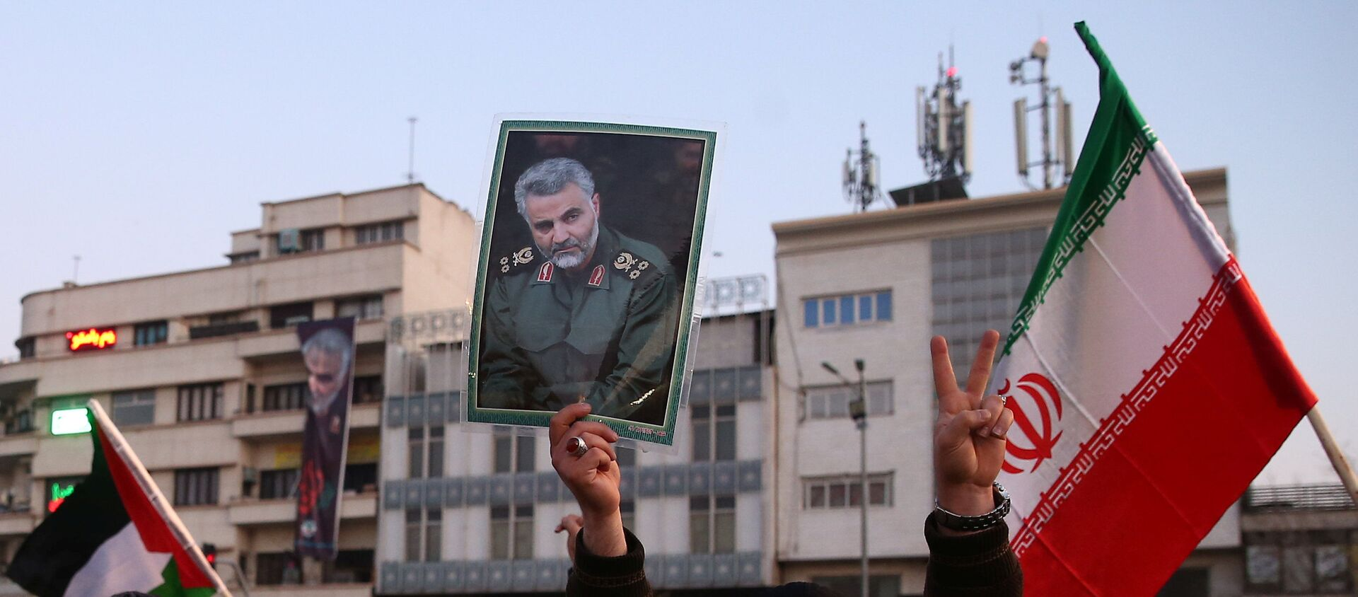 A man holds a picture of late Iranian Major-General Qassem Soleimani, as people celebrate in the street after Iran launched missiles at U.S.-led forces in Iraq, in Tehran, Iran - Sputnik International, 1920, 07.02.2020