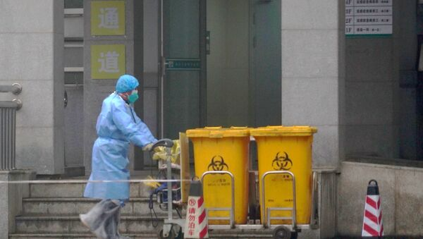 FILE - In this Wednesday, Jan. 22, 2020, file photo, a staff member moves bio-waste containers past the entrance of the Wuhan Medical Treatment Center in Wuhan, China, where some people infected with a new virus are being treated.  - Sputnik International