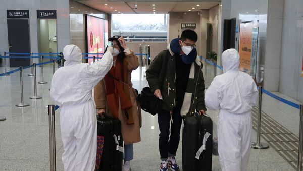 Workers in protective suits check the temperature of passengers arriving at the Xianning North Station on the eve of the Chinese Lunar New Year celebrations, in Xianning, a city bordering Wuhan to the north, in Hubei province, China January 24, 2020 - Sputnik International