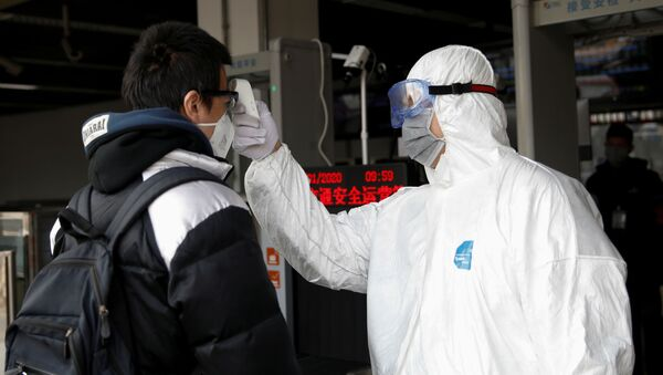 A worker in protective suit uses a thermometer to check the temperature of a man - Sputnik International