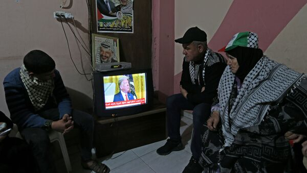 Palestinians watch a television broadcasting the announcement of Mideast peace plan by U.S. President Donald Trump, in the southern Gaza Strip January 28, 2020. REUTERS/Ibraheem Abu Mustafa - Sputnik International