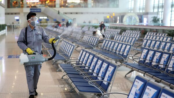 Workers in protective mask disinfects a waiting hall following the outbreak of a new coronavirus at the Nanjing Railway Station, in Nanjing - Sputnik International