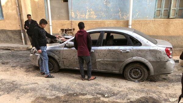 Libyan boys check a damaged car after a shell fell on a residential area at Hadba al-Badri district, in Tripoli - Sputnik International