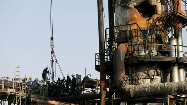 Workers are seen at the damaged site of Saudi Aramco oil facility in Abqaiq, Saudi Arabia - Sputnik International