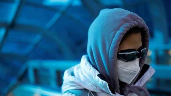 A woman wearing a face mask and goggles uses an escalator near Beijing Railway Station - Sputnik International