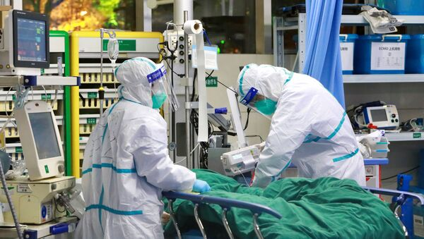 Medical staff in protective suits treat a patient with pneumonia caused by the new coronavirus at the Zhongnan Hospital of Wuhan - Sputnik International