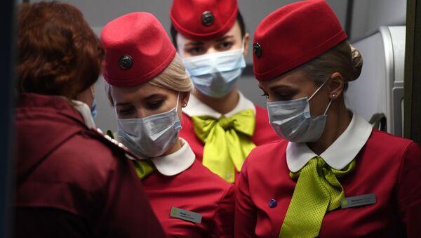 Flight attendants wearing face masks on board a S7 Airlines flight which arrived from Beijing to Novosibirsk - Sputnik International