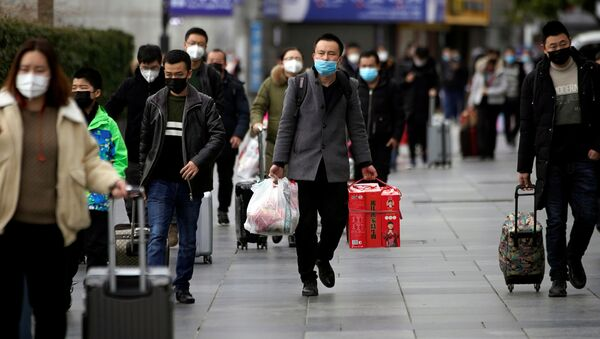 Passengers wearing masks walk outside the Shanghai railway station in Shanghai, China, as the country is hit by an outbreak of a new coronavirus, February 2, 2020 - Sputnik International
