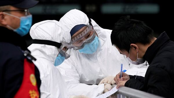 Staff members wearing protective masks check a passenger at Shanghai railway station in Shanghai, China, as the country is hit by an outbreak of a new coronavirus, February 2, 2020. - Sputnik International