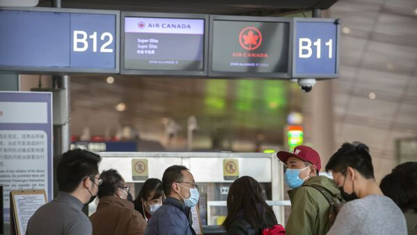 Travelers wearing face masks at the Air Canada check-in counters at Beijing Capital International Airport in Beijing - Sputnik International