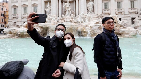 Tourists wearing protective masks take a selfie in front of the Trevi's Fountain after two cases of coronavirus were confirmed in the country, in Rome, Italy - Sputnik International