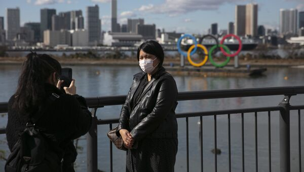 A tourist wearing a mask pauses for photos with the Olympic rings - Sputnik International