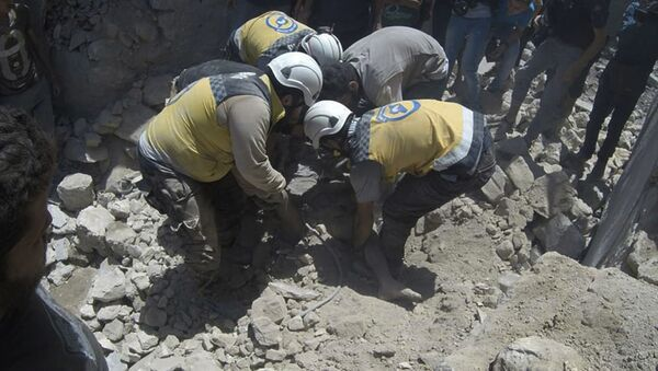 This photo provided by the Syrian Civil Defense White Helmets, which has been authenticated based on its contents and other AP reporting, shows Syrian White Helmet civil defense workers pull out a victim from under the rubble of a destroyed building that hit by a Syrian government airstrike, in the northern town of Ariha, in Idlib province, Syria, Friday, July 12, 2019 - Sputnik International
