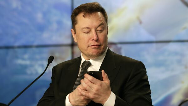 Elon Musk founder, CEO, and chief engineer/designer of SpaceX jokes with reporters as he pretends to be searching for an answer to a question on a cell phone during a news conference after a Falcon 9 SpaceX rocket test flight to demonstrate the capsule's emergency escape system at the Kennedy Space Center in Cape Canaveral, Fla., Sunday, Jan. 19, 2020. - Sputnik International