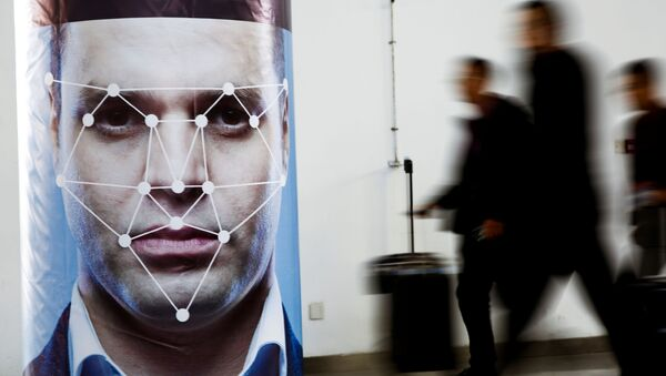 People walk past a poster simulating facial recognition software at the Security China 2018 exhibition on public safety and security in Beijing, China October 24, 2018 - Sputnik International
