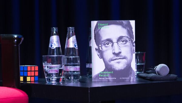 A copy of the book titled Permanent Record by US former CIA employee and whistleblower Edward Snowden is seen next to a Rubik's cube during a video conference on September 17, 2019 in Berlin. - In his book, Snowden tells among others that he used a Rubik's cube to smuggle secret data out of the rooms of the US intelligence service National Security Agency (NSA) - Sputnik International