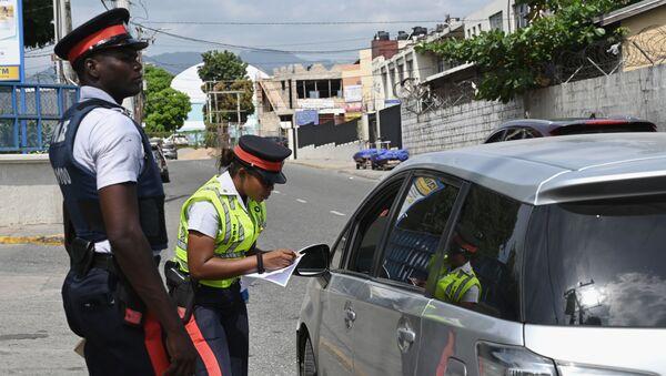Jamaican police officers check a motorist's details  - Sputnik International