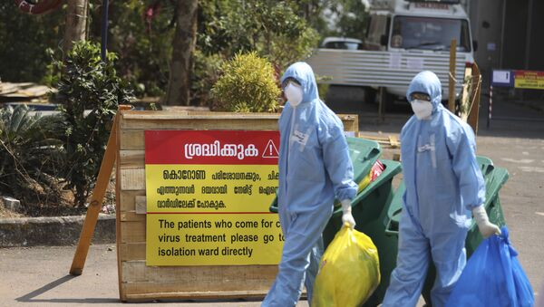 Indian workers walk with garbage after cleaning an isolation ward at a hospital for observing people suspected to have a new coronavirus infection in Kochi, Kerala state, India, Tuesday, Feb.4, 2020. - Sputnik International