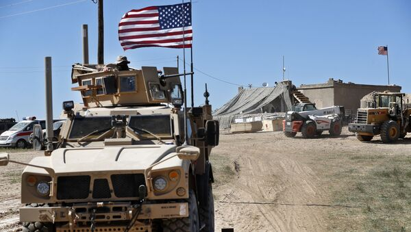 A U.S. soldier, left, sits on an armored vehicle behind a sand barrier at a newly installed position near the tense front line between the U.S-backed Syrian Manbij Military Council and the Turkish-backed fighters, in Manbij, north Syria, Wednesday, April 4, 2018.  - Sputnik International