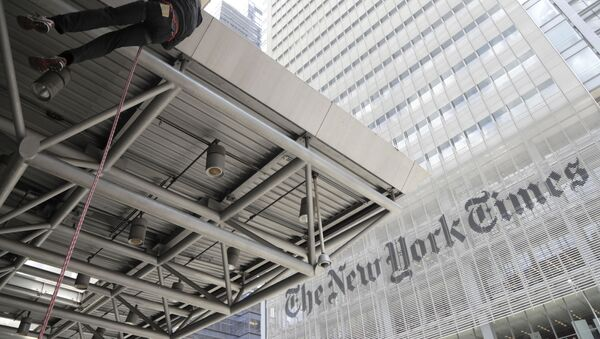 A man rappels down the side of the Port Authority Building after hanging a sign during a climate change rally outside of the New York Times building - Sputnik International