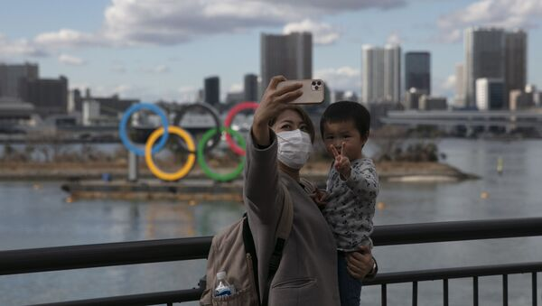 A Japanese woman and her son in front of the Olympics sign in Tokyo - Sputnik International