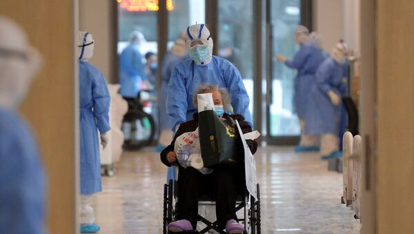 A medical worker in protective suit moves a novel coronavirus patient in a wheelchair at a hospital in Wuhan - Sputnik International