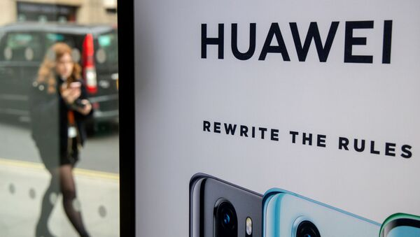 (FILES) In this file photo taken on April 29, 2019 A pedestrian walks past a Huawei product stand at an EE telecommunications shop in central London - Sputnik International