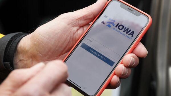 Precinct captain Carl Voss of Des Moines displays the Iowa Democratic Party caucus reporting app on his phone outside of the Iowa Democratic Party headquarters in Des Moines, Iowa, Tuesday, Feb. 4, 2020 - Sputnik International