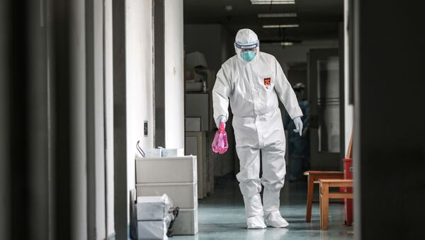 A medical worker in protective suit disinfects the hallway at Jinyintan hospital in Wuhan - Sputnik International