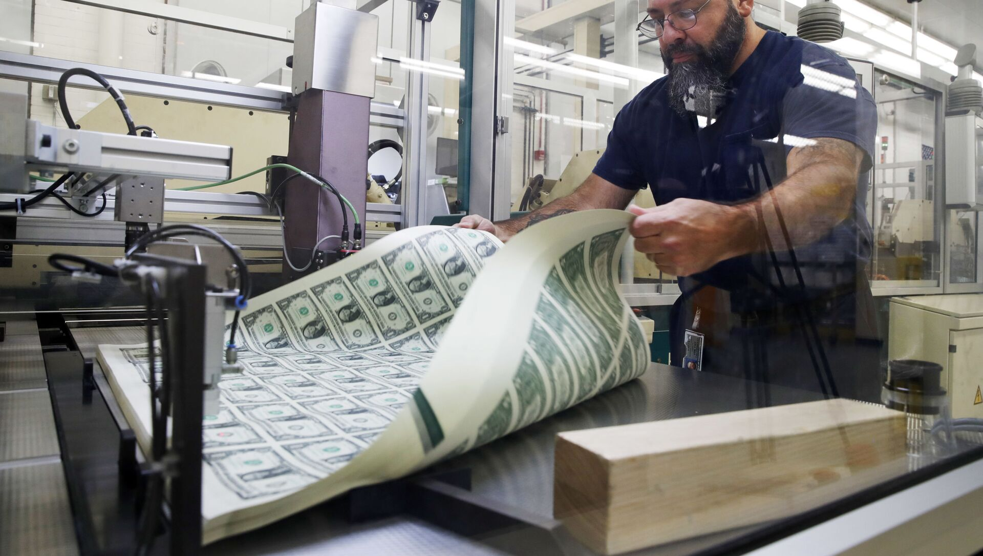 FILE- In this Nov. 15, 2017, file photo, a worker aerates printed sheets of dollar bills at the Bureau of Engraving and Printing in Washington.  - Sputnik International, 1920, 02.08.2021