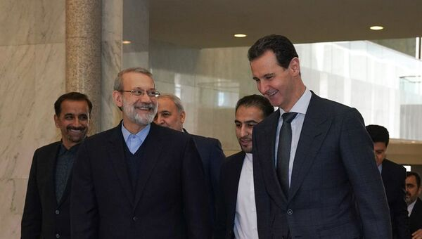 A handout picture released by the official Facebook page for the Syrian Presidency on February 16, 2020, shows Syrian President Bashar al-Assad (R) welcoming Iran's Parliament Speaker Ali Larijani in the capital Damascus - Sputnik International