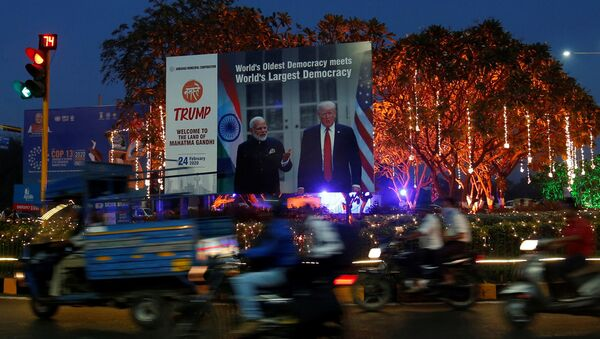 People ride their motorbikes past a hoarding with the images of India's Prime Minister Narendra Modi and U.S. President Donald Trump installed next to decorated trees alongside a road ahead of Trump's visit, in Ahmedabad, India, February 20, 2020 - Sputnik International