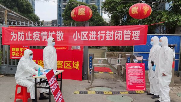 Workers in protective suits are seen at a checkpoint for registration and body temperature measurement, at an entrance to a residential compound in Wuhan, February 13, 2020 - Sputnik International