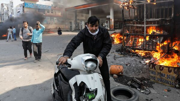 A man pushes his damaged scooter past a burning petrol pump during a clash between people supporting a new citizenship law and those opposing it, in New Delhi India, February 24, 2020 - Sputnik International