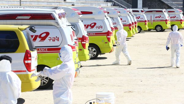 Medical workers get ready as ambulances are parked to transport a confirmed coronavirus patient in Daegu, South Korea, February 23, 2020 - Sputnik International