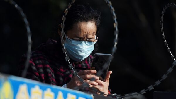 FILE PHOTO: A woman uses her mobile phone behind barbed wire at an entrance of a residential compound in Wuhan - Sputnik International