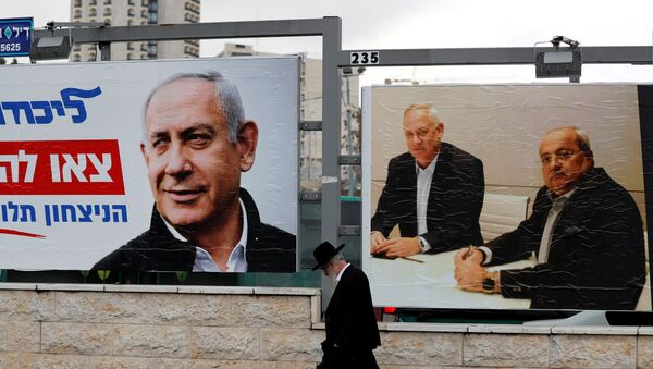 An ultra-Orthodox Jewish man walks next to Likud party election campaign banners, one depicting party leader Israeli Prime Minister Benjamin Netanyahu and the other depicting Benny Gantz, head of Blue and White party and Ahmad Tibi, co-leader of the Joint List, an Arab party, in Jerusalem February 20, 2020 - Sputnik International