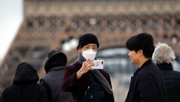 A man wears a face mask on the Trocadero esplanade in front of the Eiffel Tower in Paris, France, February 26, 2020 - Sputnik International