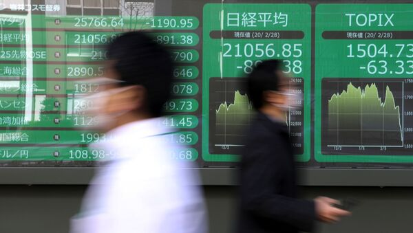 People wearing protective face masks, following an outbreak of the coronavirus, walk past a screen showing Nikkei index, outside a brokerage in Tokyo, Japan February 28, 2020. - Sputnik International