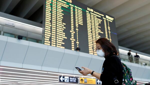 FILE PHOTO: A passenger in a protective mask uses her phone at Rome's Fiumicino airport, after first cases of coronavirus were confirmed in Italy, January 31, 2020. REUTERS/Yara Nardi/File Photo - Sputnik International