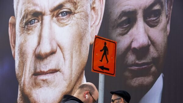 People walk past an election campaign billboard for the Blue and White party, the opposition party led by Benny Gantz, left, in Ramat Gan, Israel, Sunday, Feb. 23, 2020. Prime Minister Benjamin Netanyahu of the Likud party is pictured at right. - Sputnik International