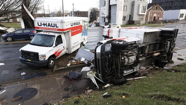 Damaged trucks sit on a sidewalk as well as the street following a deadly tornado, Tuesday, March 3, 2020, in Nashville, Tenn. Tornadoes ripped across Tennessee early Tuesday, shredding buildings and killing multiple people. - Sputnik International