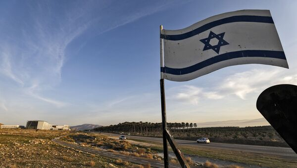 An Israeli flag hovers cars driving by the Israeli settlement of Shlomtzion in the Jordan valley in the occupied West Bank on January 27, 2020. - Sputnik International