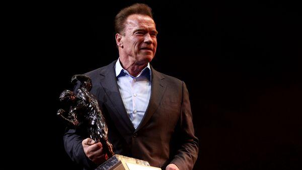 Arnold Schwarzenegger holds the Arnold Classic trophy - Sputnik International