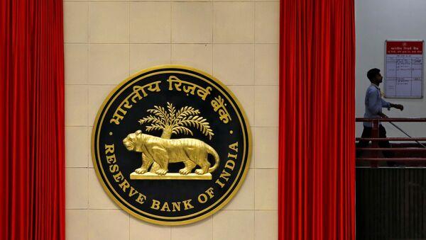 FILE PHOTO: A worker walks past the logo of Reserve Bank of India inside its office in New Delhi - Sputnik International