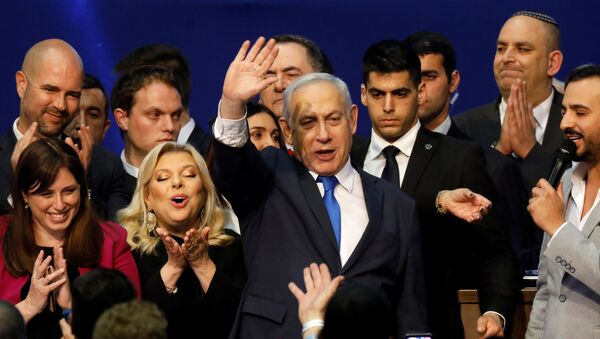 Israeli Prime Minister Benjamin Netanyahu stands next to his wife Sara as he waves to supporters following the announcement of exit polls in Israel's election at his Likud party headquarters in Tel Aviv, Israel March 3, 2020 - Sputnik International